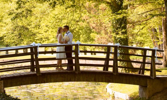 Bride and groom kissing while standing on bridge.